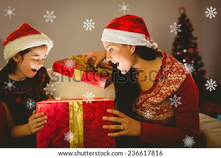 Festive mother and daughter opening a glowing christmas gift against snowflakes - stock photo