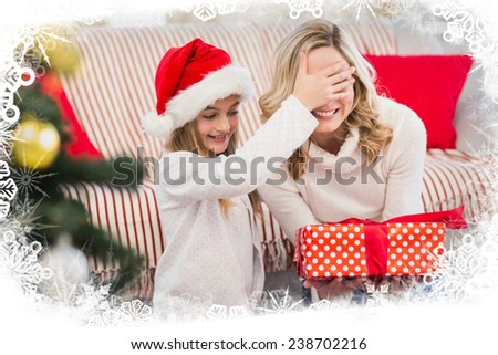 Festive mother and daughter with gift against frost frame - stock photo
