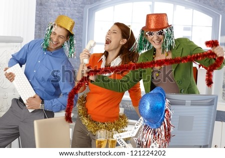 Festive new year office party, office workers having fun with accessories. - stock photo