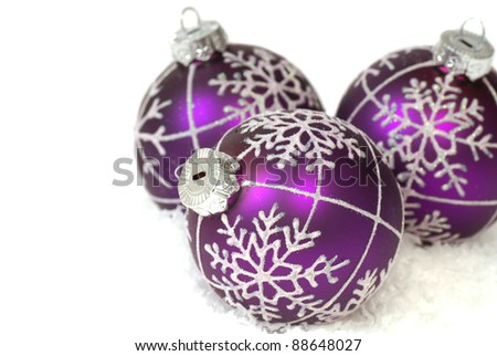 Festive purple Christmas ornaments on snowflakes - stock photo