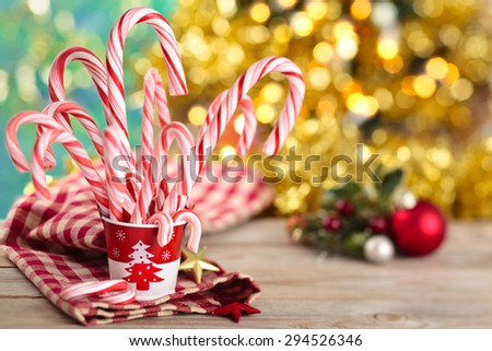 Festive red and white peppermint candy canes against  holiday lights. Focus on bucket and some of the candies. - stock photo