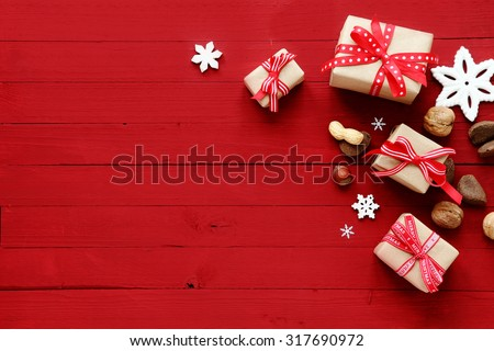 Festive red Christmas card background with copyspace and a holiday border of decorative Xmas gifts, snowflake ornaments and assorted fresh whole nuts - stock photo