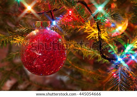 Festive red glitter Christmas bauble hanging on a natural spruce branch with star shaped lights effect - stock photo
