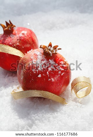 Festive ripe red pomegranates with decorative gold ribbon nestling in fresh winter snow with copyspace for your Christmas greeting - stock photo