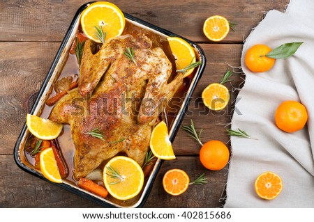 Festive roast duck with citrus, vegetables and rosemary on rustic wooden background. Top view - stock photo