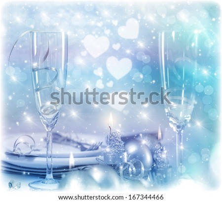 Festive romantic table setting, Christmas eve in restaurant, white utensil served with silver cutlery, candle light and decorative shiny baubles - stock photo
