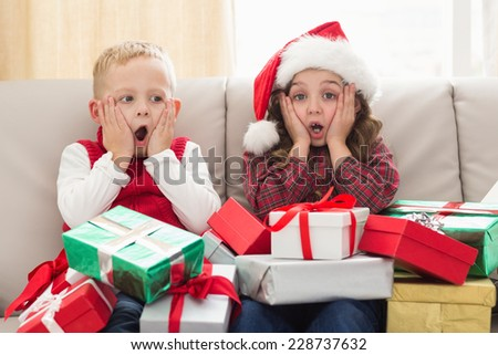 Festive siblings surrounded by gifts at home in the living room - stock photo
