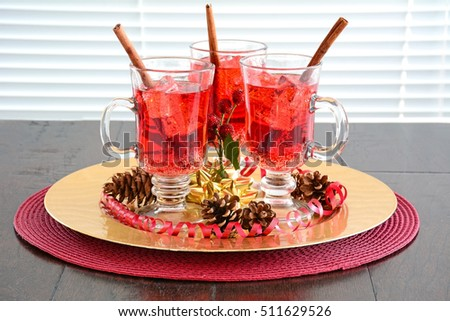Festive sparkling red cranberry soda drinks with cinnamon stir sticks in red and gold themed accents.  Shallow depth of field with focus on bubbles.