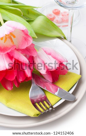 Festive spring table setting with pink tulips, napkins in bright colors, closeup - stock photo