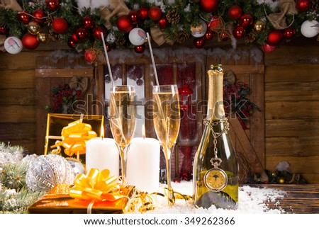 Festive Still Life - Bottle of Champagne with Two Full Glasses on Snow Covered Surface with Lit Candles and Gold Wrapped Gifts in front of Rustic Wood Cabin Decorated for Christmas - stock photo