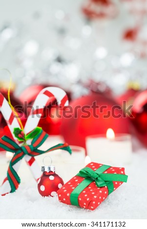 Festive Still Life of Miniature Red and White Polka Dot Wrapped Gift Box, Christmas Ball and Candy Canes in front of Shiny Red Balls on Snowy Surface with Burning Candle - stock photo