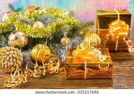Festive Still Life of Two Gifts Wrapped in Gold Paper and Bows on Wooden Table Beside Christmas Pine Decoration with Gold Balls - stock photo