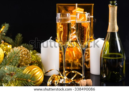 Festive Still Life - Two Glasses of Sparkling Champagne on Black Background with Bottle, White Candles, Gold Wrapped Gifts and Evergreens Decorated with Christmas Balls - stock photo