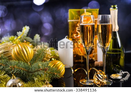 Festive Still Life - Two Glasses of Sparkling Champagne with Bottle, Candles, Gifts and Christmas Decorations on Black Background - stock photo