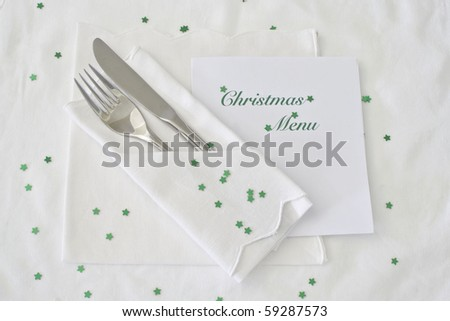 Festive table place setting with shiny green stars and Christmas  menu - stock photo