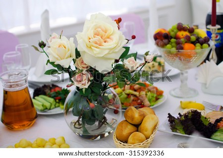 Festive table setting. Banquet table, Serving dishes, Food restaurant. White roses in a vase. Wedding evening. The peoples kitchen. Range of snacks. Decor with white tablecloth. The Christmas table.  - stock photo