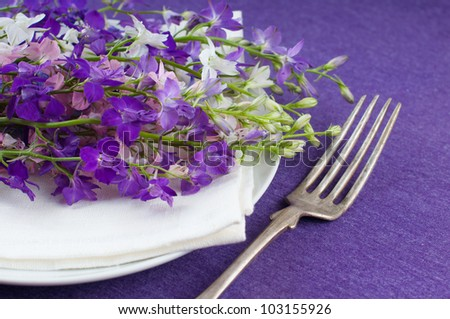 Festive table setting, plate, fork and a bouquet of flowers on purple background - stock photo
