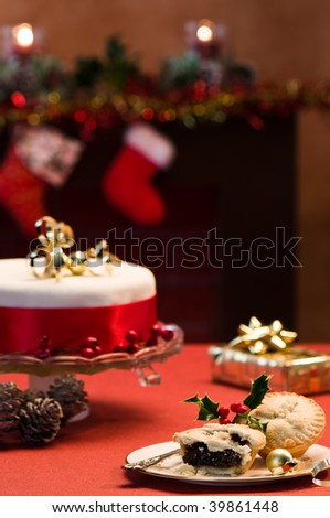 Festive table setting with Christmas cake and mince pies, decorated fireplace in background with lit candles - stock photo