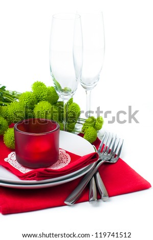Festive table setting with chrysanthemums, glasses, candles, napkins and cutlery in red and green colors