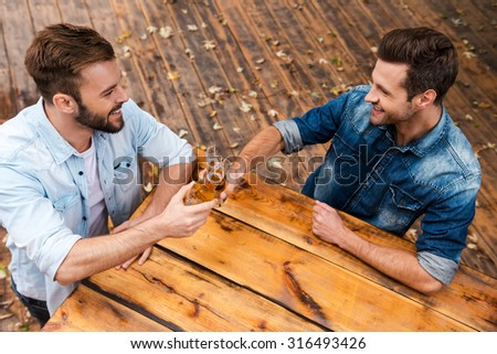Festive time with best friend. Top view of two cheerful young men clinking glasses with beerand smiling while standing outdoors  - stock photo