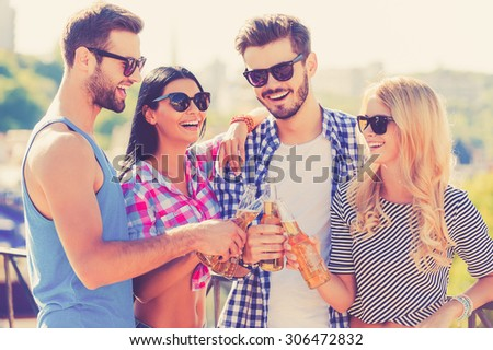 Festive time with friends. Group of happy young people clinking glasses with beer and bonding to each other while standing on the roof - stock photo