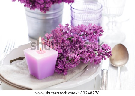 Festive wedding table setting with lilac flowers, candles, vintage cutlery, glasses and dishes - stock photo