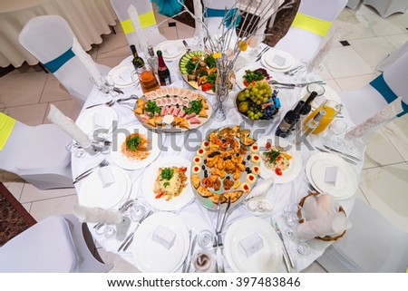 festive white table with food and drinks in the restaurant for a wedding event - stock photo