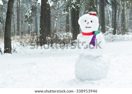 Festive winter three snowball snowman with striped hat and scarf - stock photo