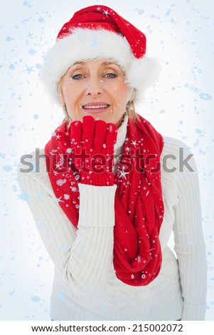 Festive woman blowing a kiss against snow falling - stock photo