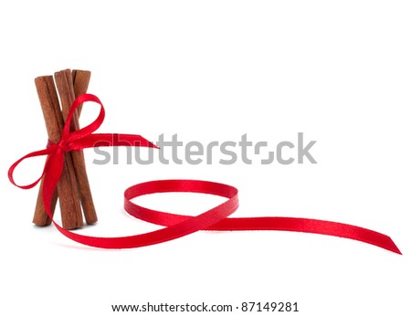 Festive wrapped cinnamon sticks isolated on white background - stock photo