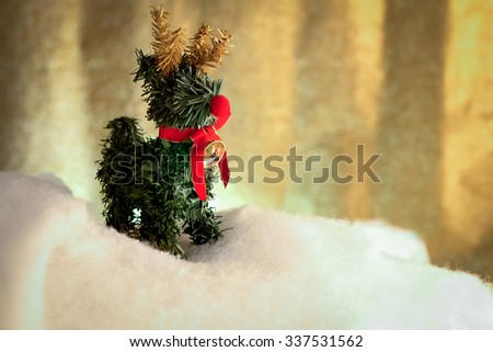 Festive yellow and gold Christmas background with elegant deer with red ribbon on snow floor - stock photo
