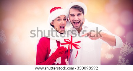 Festive young couple holding gift against glowing christmas background - stock photo