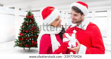 Festive young couple holding gift against home with christmas tree - stock photo