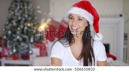 Festive young woman in red Santa Claus hat