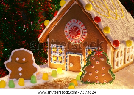 festively lit homemade gingerbread house with snowman, Christmas tree and decorations - stock photo