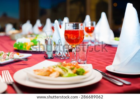 Festively served banquet table with glasses and salads. - stock photo