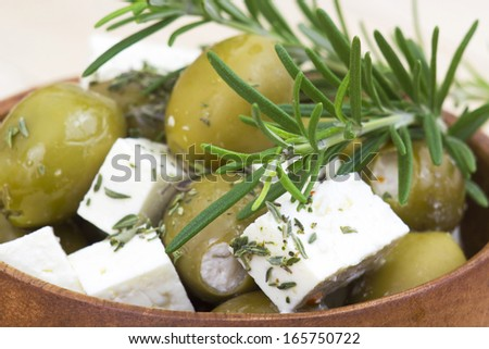 feta cheese and olives with herbs in olive oil - stock photo