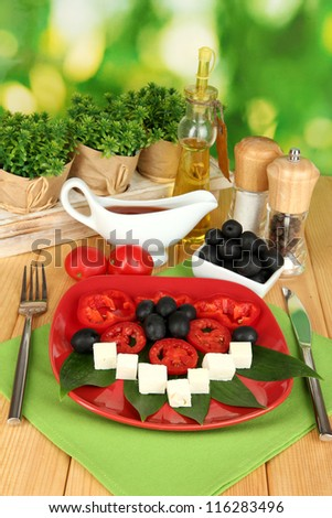 Feta cheese on plate decorated with spices and oil on wooden table on natural background
