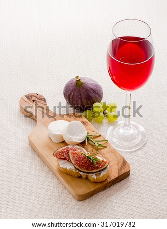 Feta cheese with ripe fig and red wine, close up