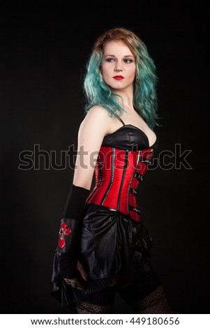 Fetish alternative looking model with colored hairs on black background in studio photo - stock photo