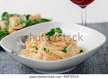 Fettuccine Alfredo with Ceasar Salad and wine - stock photo