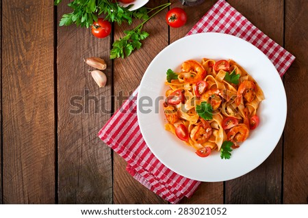 Fettuccine pasta with shrimp, tomatoes and herbs. Top view - stock photo