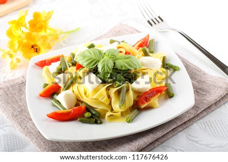 Fettuccine with green beans, mozzarella and tomato on complex background