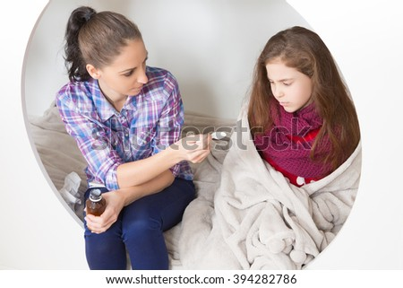 Fever, cold and flu concepts. Young mother holding medicines in her hand, but little daughter does not want to accept them. - stock photo