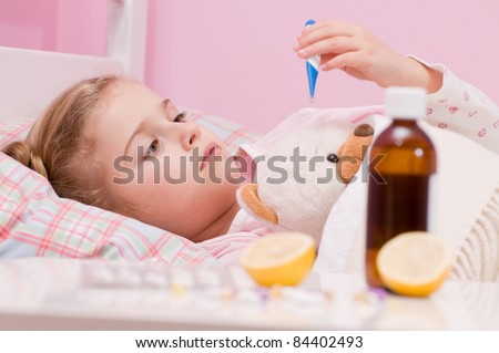 Fever, cold and flu - Medicines and hot tea in front, sick girl with teddy bear in bed ( No-name teddy bear ) - stock photo