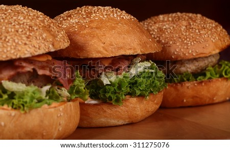 Few appetizing big delicious fresh burgers with green lettuce red tomato cheese and bacon slice and white bread bun with sesame seeds on black background closeup, horizontal picture - stock photo
