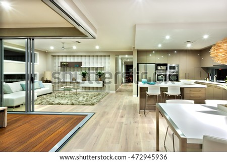 Few areas of luxury house included living room and kitchen. The wooden floor is spread to the whole house and a way to the outside, there are kitchenware like a fridge and ovens with a faucet