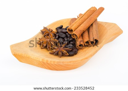 Few cinnamon sticks with star anise and coffee beans on wooden plate and white background - stock photo