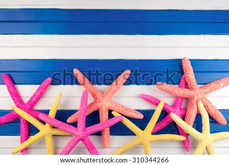 Few colorful sea stars on a wooden background. - stock photo