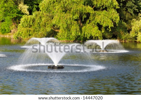 few fountains on the pond in the park - stock photo